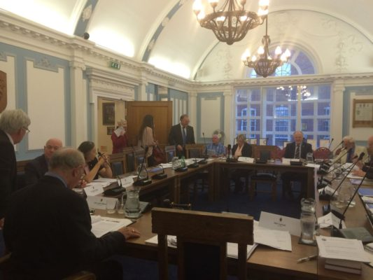 Council meeting. People sitting at desks in a formal setting.