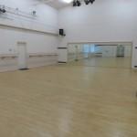 Inside of dance studio. Mirrored wall and wooden floor