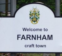 Road sign, with black writing and town council crest.