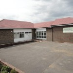 Outside of single storey L shaped community hall. Brick, red tiled roof.
