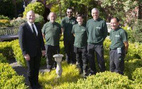 Man in suit with five men in green uniform standing in a garden