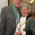 Man in suit stands next to female Mayor in robes.
