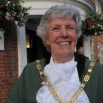 Head and shoulders of female Mayor dressed in green Mayoral robes and chain.