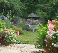 Large garden, flower beds to left and right, summer house and bench in background and patio in foreground.